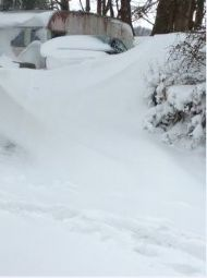 Car buried in snow opposite Rainbow Inn