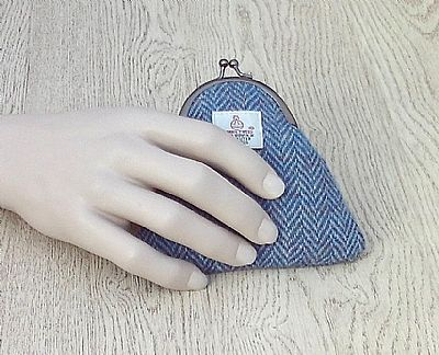 holding blue herringbone purse
