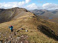 Margaret approaching the summit of Creag a' Mhaim. Druim Shionnach behind.