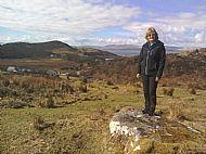 woman standing on rock overlooking carsaig bay